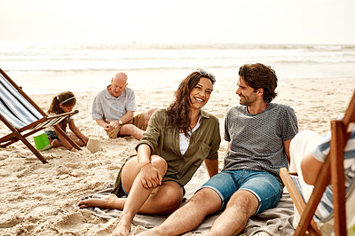 Buy stock photo Shot of a young couple relaxing together at the beach with their daughter and her granddad playing in the background