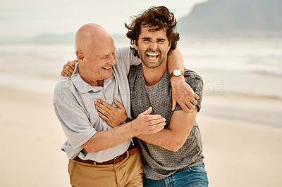 Buy stock photo Portrait of a handsome young man spending the day with his father at the beach