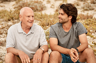 Buy stock photo Shot of a cheerful senior man and his adult son spending time together at the beach