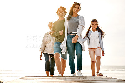 Buy stock photo Full length shot of a beautiful extended family walking together at the beach during the day