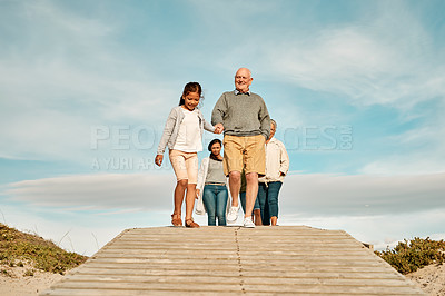 Buy stock photo Full length shot of an adorable little girl walking with her grandfather on the beach