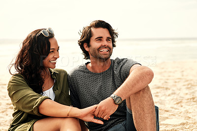 Buy stock photo Shot of an affectionate young couple spending time together at the beach