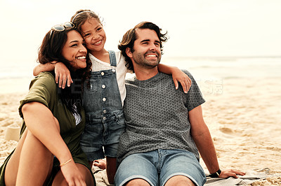 Buy stock photo Shot of a beautiful young family of three spending the day together at the beach