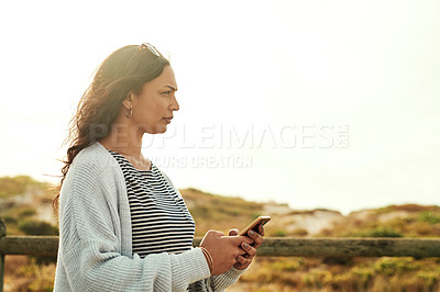 Buy stock photo Shot of a beautiful young woman using her cellphone while relaxing in the outdoors