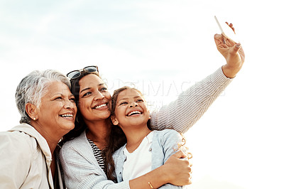 Buy stock photo Shot of a beautiful young woman taking a selfie with her senior mother and young daughter at the beach