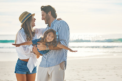 Buy stock photo Cropped shot of an affectionate couple playing with their daughter during an enjoyable day out on the beach