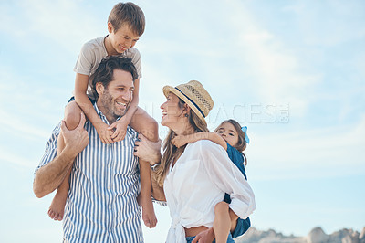 Buy stock photo Cropped shot of an affectionate couple carrying their two children during an enjoyable day out on the beach