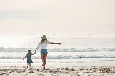 Buy stock photo Rearview shot of an affectionate young mother holding her daughter's hand and walking towards the sea during a day out