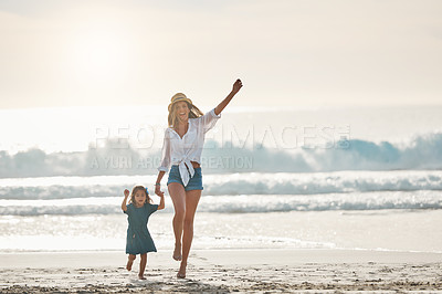 Buy stock photo Full length portrait of an affectionate young mother holding her daughter's hand and walking on the beach
