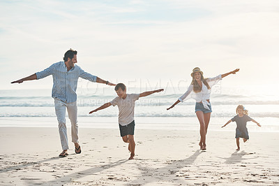 Buy stock photo Full length shot of a happy young couple enjoying a playful day out with their two children on the beach