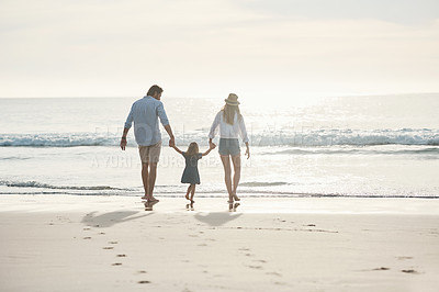 Buy stock photo Rearview shot of an unrecognizable couple holding hands with their little daughter and walking on the beach together
