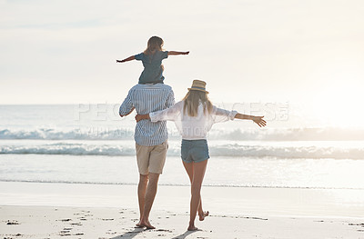 Buy stock photo Rearview shot of an unrecognizable father carrying his daughter on his shoulders and walking on the beach with his wife