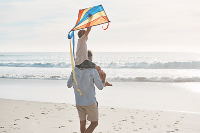 Buy stock photo Rearview shot of a young boy being carried on his father's shoulders and holding a kite on the beach