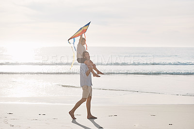 Buy stock photo Full length shot of a young boy being carried on his father's shoulders and holding a kite on the beach