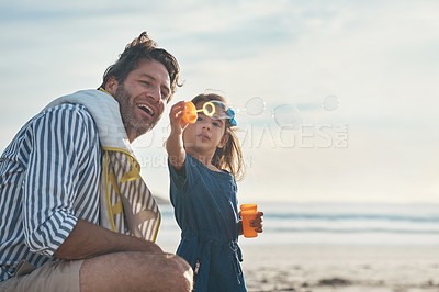 Buy stock photo Cropped shot of a playful mature father blowing bubbles with his daughter during a day out on the beach together