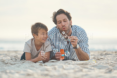 Buy stock photo Full length shot of a playful mature father lying on the beach and blowing bubbles with his son