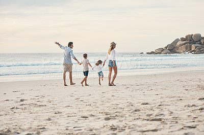 Buy stock photo Full length shot of a happy couple holding hands with their two children and walking along the beach