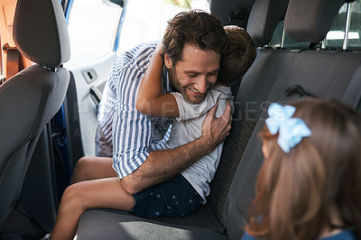 Buy stock photo Cropped shot of a young boy sitting in the car and hugging his affectionate father before going on a roadtrip