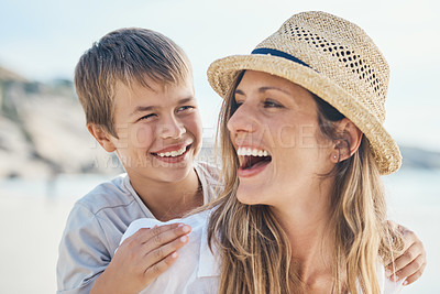 Buy stock photo Cropped shot of an attractive young mother bonding with her son and giving him a piggyback ride on the beach