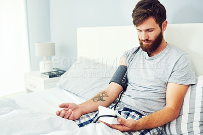 Buy stock photo Cropped shot of a young man checking his blood pressure at home
