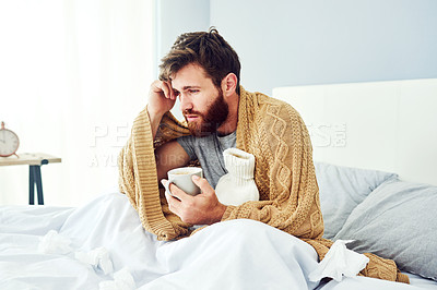 Buy stock photo Shot of a young man sitting in bed while suffering with flu