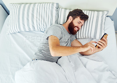 Buy stock photo Cropped shot of a young man using his cellphone while relaxing in his bedroom