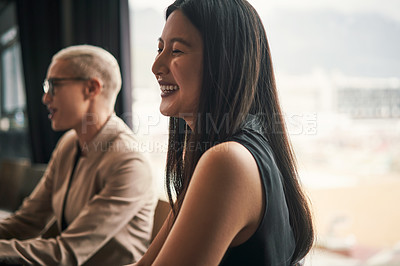Buy stock photo Shot of an attractive young businesswoman laughing and feeling cheerful during a meeting with colleagues at work