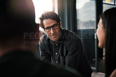 Buy stock photo Shot of a mature businessman discussing ideas with his colleagues during a meeting at work