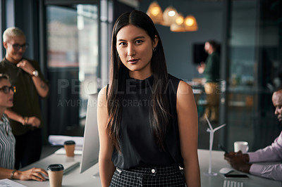 Buy stock photo Portrait of an attractive young businesswoman standing inside an office with her colleagues working in the background