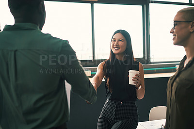 Buy stock photo Shot of an attractive young businesswoman shaking hands with a colleague at work