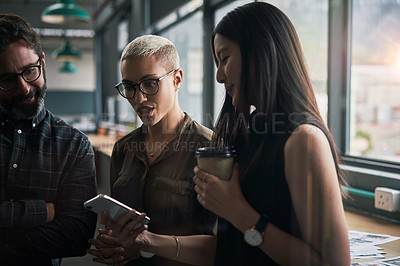 Buy stock photo Shot of a group of businesspeople using a cellphone together at work