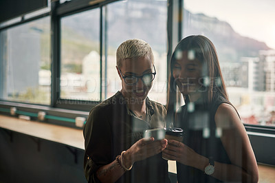 Buy stock photo Shot of two attractive young businesswomen using a cellphone together at work