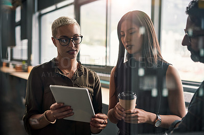 Buy stock photo Shot of a group of businesspeople using a digital tablet together at work