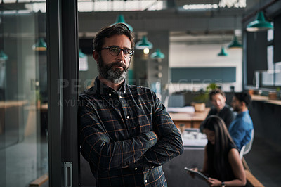 Buy stock photo Portrait of a mature businessman standing inside an office with his colleagues working in the background