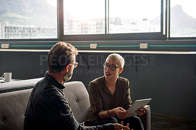 Buy stock photo Shot of two businesspeople using a digital tablet together at work