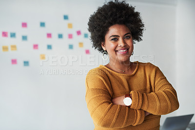 Buy stock photo Portrait of an attractive young businesswoman posing with her arms folded at work