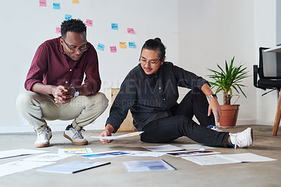 Buy stock photo Full length shot of two young businessmen sitting down on the floor and going over paperwork together at work