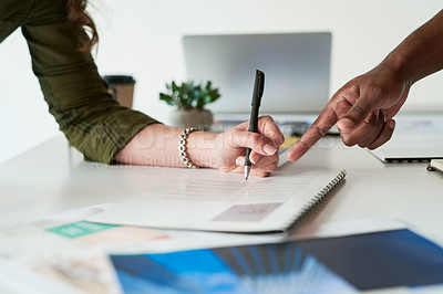 Buy stock photo Shot of two unrecognizable business people planning and going over paperwork and ideas together a work