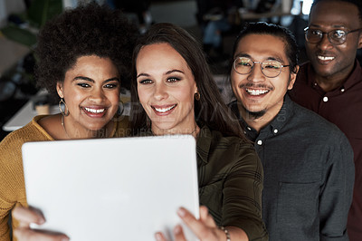 Buy stock photo Shot of a group of young businesspeople taking selfies together with a digital tablet at work