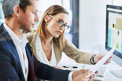 Buy stock photo Shot of two businesspeople going through paperwork while using a computer in an office
