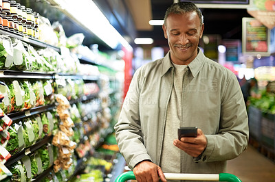 Buy stock photo Shot of a mature man using his cellphone while out shopping in a grocery store