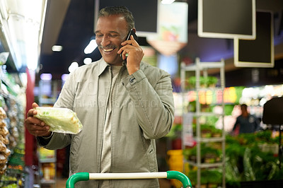 Buy stock photo Cropped shot of a mature man talking on his cellphone while out shopping in a grocery store