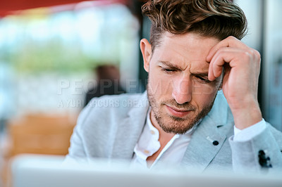 Buy stock photo Shot of a young businessman using a laptop in a cafe and looking stressed