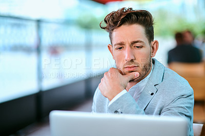 Buy stock photo Shot of a young businessman using a laptop in a cafe