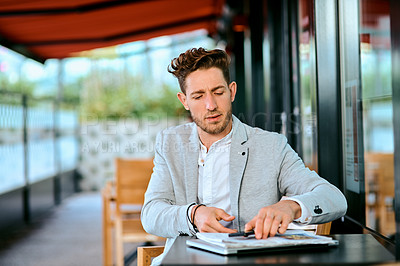 Buy stock photo Shot of a young businessman sitting at a table in a cafe