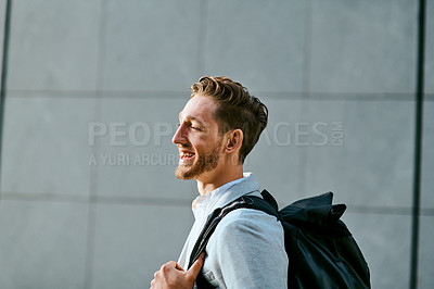 Buy stock photo Shot of a young businessman walking through a city