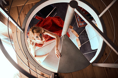 Buy stock photo Shot of a glamorous young woman dressed in elegant wear climbing up a staircase
