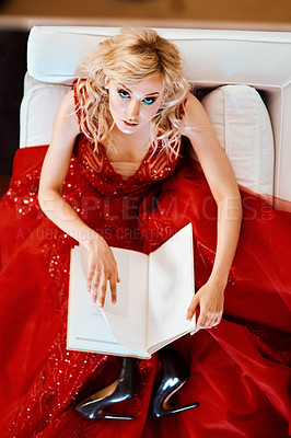 Buy stock photo Shot of a glamorous young woman dressed in elegant wear reading a book on a sofa