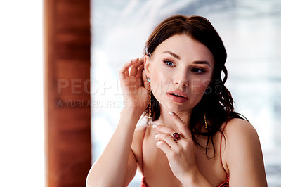 Buy stock photo Shot of a glamorous young woman admiring herself in a mirror