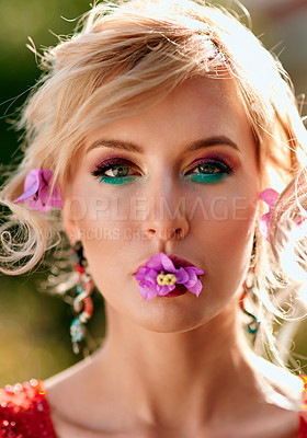 Buy stock photo Shot of a glamorous young woman with flowers in her mouth outdoors